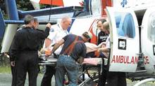 B.C. Ambulance Service paramedics and a volunteer firefighter place an injured person into an Air Ambulance helicopter on Nanaimo River Road south of Nanaimo, BC, Sunday, July 13, 2003. (Mark Brett/CP)