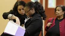 In a Jan. 28, 2012 file photo, job seekers Cameo Taylor, left, and Angelique McGuire, center, both of San Francisco, wait in line to register at a Career Fair event in San Francisco. (Eric Risberg/AP)