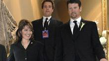 Former U.S. vice-presidential candidate Sarah Palin and husband Todd Palin, right, walk down a set of stairs to the dinning hall in Hamilton, Ont., on April 15, 2010. (Sheryl Nadler/THE CANADIAN PRESS)