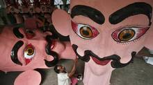 FACE IN THE CROWD: An artist applies finishing touches to an effigy of the demon king Ravana for the Hindu festival of Dussehra in Chandigarh, India. (AJAY VERMA/REUTERS)