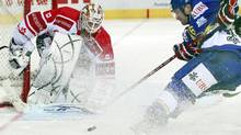 Team Canada's goalkeeper Jeff Deslauriers (L) is challenged by Paolo Duca of HC Davos scores during their ice hockey match at the Spengler Cup tournament in the Swiss mountain resort of Davos December 28, 2010 (ARND WIEGMANN)