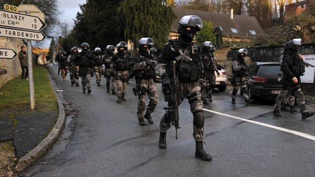 French police special forces walk in Corcy, northern France, on January 8, 2015 as they carry out searches.