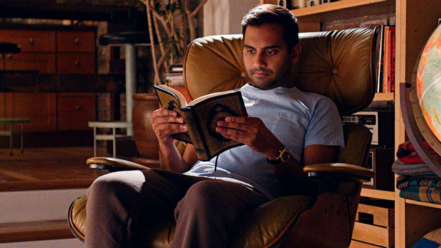 Dev from Netflix's Master of None sits in a classic Eames chair in his apartment.