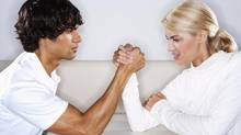 Young man and woman sitting at table face to face, arm wrestling (Thomas Northcut/Getty Images)