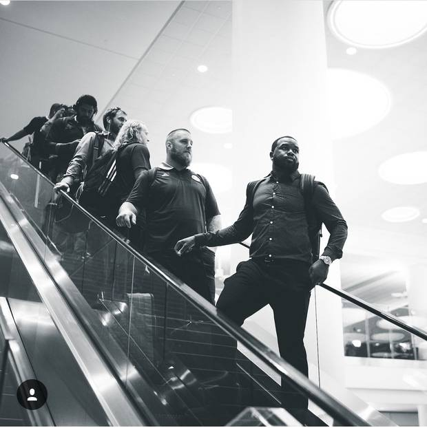 The Toronto Argonauts descend an escalator at the Winnipeg airport.