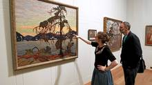 "Exhibition officer Amy Concannon (L) and designer Eric Pearson view Canadian artist Tom Thomson's 1917 oil painting ""The Jack Pine"" at the Dulwich Picture Gallery in London on Oct. 14, 2011. The gallery is hosting ""Painting Canada: Tom Thomson and the Group of Seven"" from Oct. 19, 2011 to Jan. 8, 2012. (Chris Helgren/Reuters/Chris Helgren/Reuters)"