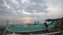 Filipino fishermen check on their boats that are docked on top of piles of garbage as they prepare for a coming storm along a coastal village in Navotas, north of Manila, on July 14, 2014. (AARON FAVILA/ASSOCIATED PRESS)