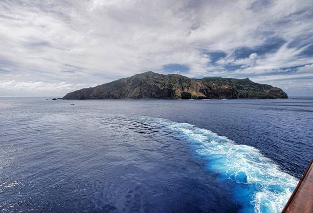 A ship turns as it passes a Pacific island.