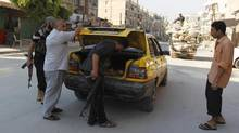 Free Syrian Army members search a car at a checkpoint in the district of Al Sukari in Aleppo on Aug. 9, 2012. (ZOHRA BENSEMRA/REUTERS)