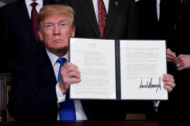 U.S. President Donald Trump holds his signed memorandum on intellectual property tariffs on high-tech goods from China, at the White House in Washington, March 22, 2018.