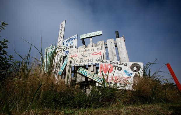 Handmade anti-pipeline signs are seen on the side of a road in the First Nations village of Old Massett, B.C.