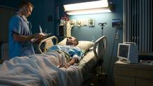 Doctor examining patient in hospital room (Thomas Northcut/Getty Images)