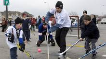 David Sasson, centre, received a $75 fine after refusing to break up a street hockey game in Montreal. (Robert Skinner/THE CANADIAN PRESS/La Presse-Robert Skinner)