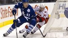 Toronto Maple Leaf Jake Gardiner is chased by Carolina Hurricane Drayson Bowman during first period NHL action in Toronto on Tuesday December 13, 2011. (Pawel Dwulit/The Canadian Press)