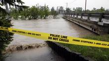 A police line closes off access to a footpath and a bridge that lead to the Calgary Zoo, Friday, June 21, 2013. Heavy rains have caused flooding, closed roads, and forced evacuations. (Jeff McIntosh/THE CANADIAN PRESS)