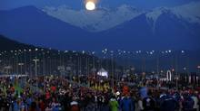 The moon rises over the mountains behind the public entrance to the Olympic Park at the Sochi 2014 Winter Olympics February 14, 2014. (BRIAN SNYDER/REUTERS)