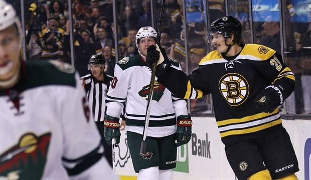Boston Bruins left wing Loui Eriksson, right, skates past Minnesota Wild defenseman Ryan Suter, center, after scoring his first goal of the game during the second period of an NHL hockey game in Boston Thursday, Nov. 19, 2015. Eriksson had a hat trick in the game. (AP Photo/Charles Krupa)