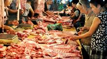 People purchase meat from a market on August 09, 2011 in Jinhua, Zhejiang Province of China. (ChinaFotoPress/Getty Images)