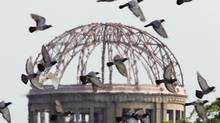 Doves flutter over the gutted A-bomb dome at an anniversary ceremony in Hiroshima, Japan on August 6, 2005, marking the 60th anniversary of the world's first atomic bombing of the city. (ERIKO SUGITA/REUTERS)