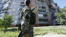 A pro-Russian fighter points to an apartment block damaged by shelling in Slaviansk in eastern Ukraine June 29, 2014. (SHAMIL ZHUMATOV/REUTERS)