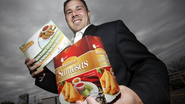 Sunpeak Foods Inc. founder Regan Stevenson holds boxes of the company's chicken and samosa products at its Winnipeg warehouse. (JOHN WOODS FOR THE GLOBE AND MAIL)