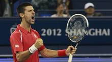 Novak Djokovic of Serbia celebrates after winning a game against Andy Murray of Britain in the men's singles at the Shanghai Masters tennis tournament at Qizhong Forest Sports City Tennis Center in Shanghai, China, Sunday Oct. 14, 2012. Djokovic won 5-7, 7-6(11), 6-3. (Eugene Hoshiko/AP)