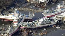 Fishing boats rest piled up on debris in the northern Japanese city of Kesennuma in Miyagi prefecture on March 12, 2011 a day after a massive 8.9 magnitude quake and tsunami hit the region. (YOMIURI SHIMBUN)