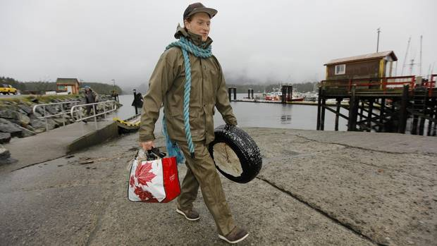 Connor Paone cleans up debris, including a discarded tire, during the Surfrider Pacific Rim Christmas Jingle Cleanup Event along the Tofino harbour shorefront near the 4th Street government dock and marina on December 2, 2016.