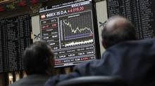 Traders looks at screens at the Madrid bourse April 23, 2012. (ANDREA COMAS/ANDREA COMAS/REUTERS)