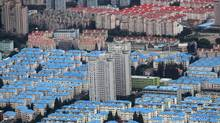 Residential buildings are seen in the Pudong district of Shanghai in this October 26, 2011 file photo. Property is a touchstone issue in the world's second-biggest economy, generating around 10 per cent of China's GDP. Besides would-be buyers and profit-hungry developers, local governments across the country rely on income from land sales to service debts estimated at 10.7 trillion yuan ($1.7-trillion) and fund construction of roads, railways and schools. (CARLOS BARRIA/CARLOS BARRIA/REUTERS)