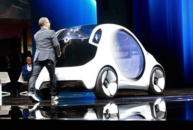 A man pushes an electric Smart concept car which broke down at the Mercedes-Benz press conference at the 2017 Frankfurt Auto Show.