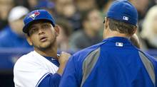 Toronto Blue Jays starting pitcher Henderson Alvarez checks his neck with manager John Farrell (right) after getting hit by an errant throw during second inning AL action against the Tampa Bay Rays in Toronto on Thursday April 19, 2012. (Frank Gunn/THE CANADIAN PRESS)
