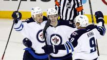 Winnipeg Jets centre Olli Jokinen, left, is congratulated by teammates James Wright and Evander Kane in the second period of their NHL hockey game against the New York Rangers at Madison Square Garden in New York, February 26, 2013. (ADAM HUNGER/REUTERS)