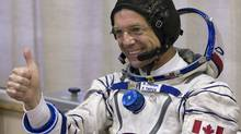 Canadian astronaut Bob Thirsk gives a thumbs-up after putting on his space suit before launch in May. (SHAMIL ZHUMATOV)