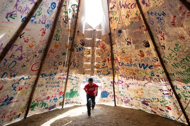 Jesse Jaso, 12, enters the Unity Teepee, at the Sacred Stone Camp near Cannon Ball. Supporters from all across North America and around the world have left signatures and messages on the teepee.