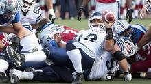 Toronto Argonauts' quarterback Jarious Jackson lies on players after making a play during second half CFL football against the Montreal Alouettes in Montreal, Sunday, September 23, 2012. (Graham Hughes/THE CANADIAN PRESS)
