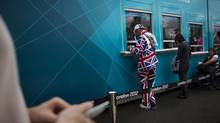 Visitors by their tickets for the Olympic Park at the 2012 Summer Olympics (Emilio Morenatti/The Associated Press)