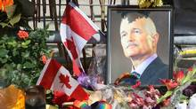 A portrait of the late NDP Leader Jack Layton sits in flowers at a makeshift memorial outside Toronto City Hall on Friday, Aug. 26, 2011. (Ryan Remiorz/CP/Ryan Remiorz/CP)