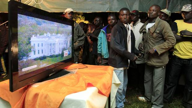 Residents stand next to a television set as they follow the voting process during the U.S. presidential elections in the ancestral home of U.S. President Barack Obama in Nyangoma Kogelo, 430 km west of Kenya's capital Nairobi, November 6, 2012. (Thomas Mukoya/Thomas Mukoya)