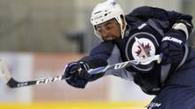 Winnipeg Jets player Dustin Byfuglien takes a shot during the NHL team's training camp in Winnipeg, September 17, 2011. REUTERS/Fred Greenslade (Fred Greenslade/Reuters)