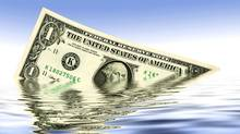A dollar in the water on blue background (Thinkstock)