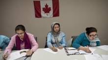 Marijam, Horia and Farida (left to right), all from Afghanistan, take part in a Canadian citizenship class June 28, 2012 at the Afghan Women's Organization in Toronto. (Moe Doiron/The Globe and Mail)