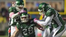 Saskatchewan Roughriders linebacker Diamond Ferri, left, and defensive end Ricky Foley, right, congratulate linebacker Craig Butler on an interception against the B.C. Lions during the second quarter of CFL action in Regina, Sask., Saturday, October 19, 2013. (Liam Richards/The Canadian Press)