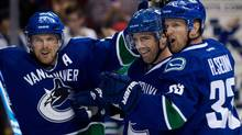 Vancouver Canucks' Daniel Sedin, Dan Hamhuis and Henrik Sedin celebrate (DARRYL DYCK/THE CANADIAN PRESS)