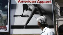 People passing by near Yonge and Gould streets in Toronto look up at an American Apparel store billboard. (Deborah Baic/The Globe and Mail)