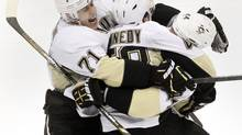 Pittsburgh Penguins' Brooks Orpik (R) is embraced by teammates Evgeni Malkin (L) and Tyler Kennedy (C) after his overtime goal against the New York Islanders during their Stanley Cup playoffs Eastern Conference quarter-final game in Uniondale, New York, May 11, 2013. (SHANNON STAPLETON/Reuters)
