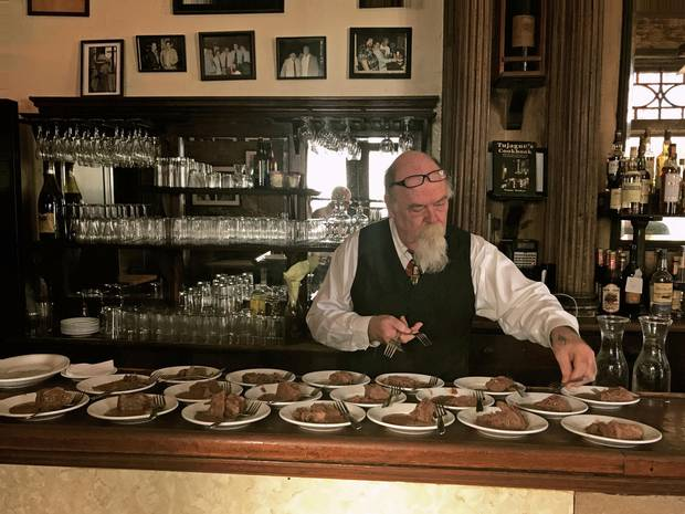 A bartender at Tujague's plates braised beef, prepared using Elizabeth Begue's original recipe.
