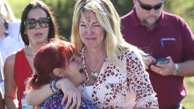 Parents wait for news after reports of a shooting at Marjory Stoneman Douglas High School in Parkland, Fla., on Feb. 14, 2018.