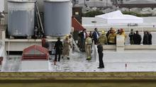 Authorities stand on the rooftop of the Cecil Hotel after a body was found in a water tank in Los Angeles on Feb. 19, 2013. (Jonathan Alcorn/Reuters)