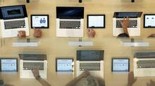 Customers look at MacBook Pros during the official opening of the largest Apple shop in southern Europe, at Passeig de Gracia in Barcelona in this July 28, 2012, file photo. (ALBERT GEA/REUTERS)